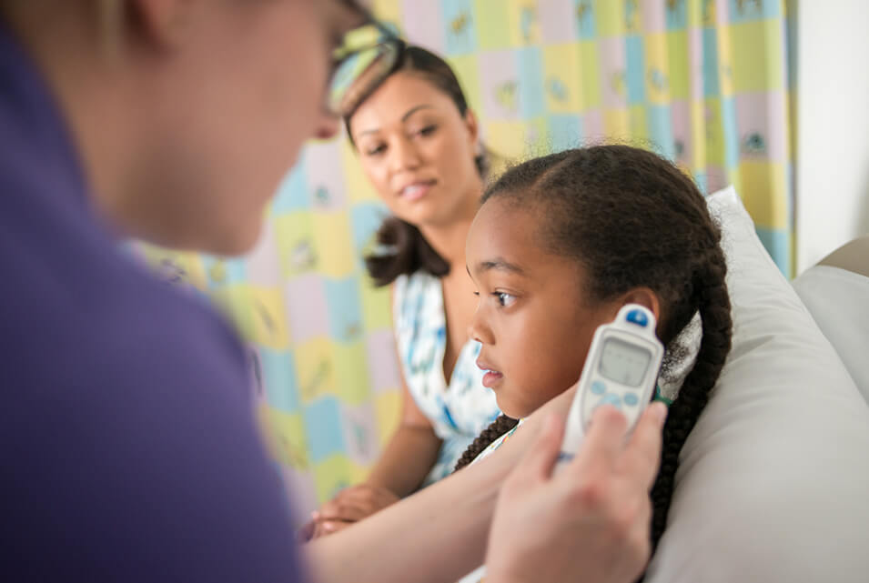Nurse taking child's temperature with ear thermometer