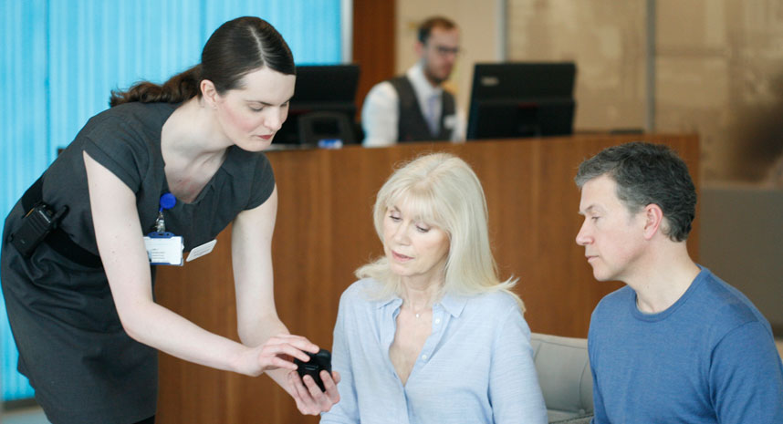 Receptionist checking patients in using mobile app