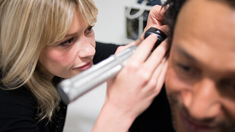 GP looking into patient's ear